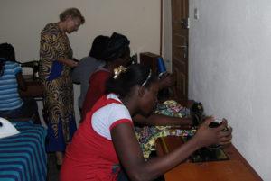 Mädchen lernen an Tret-Nähmaschinen