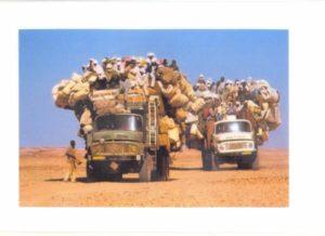 Mit Last überquellend bepackter Lastwagen, obenauf Passagiere, in der Wüste