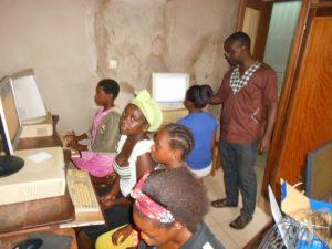 Mädchen am Computer mit Lehrer